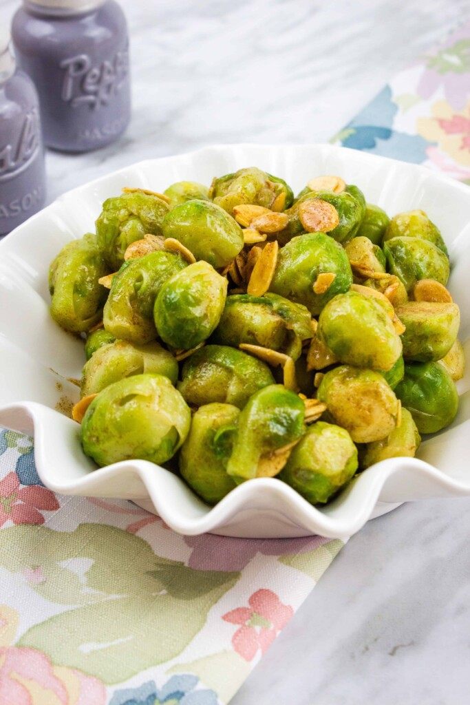 brussels sprouts with almonds and brown butter in a fluted serving bowl