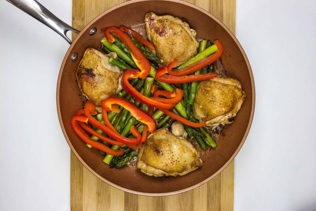 asparagus and red pepper added to chicken in the skillet