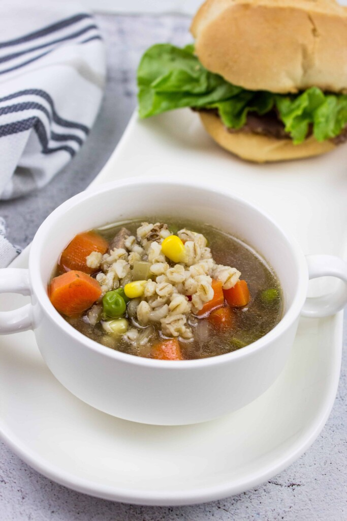 a bowlful of homemade beef & barley soup in a white bowl on a plate with a sandwich in the background