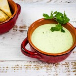 jalapeno dip in a rustic red bowl with chips in the background