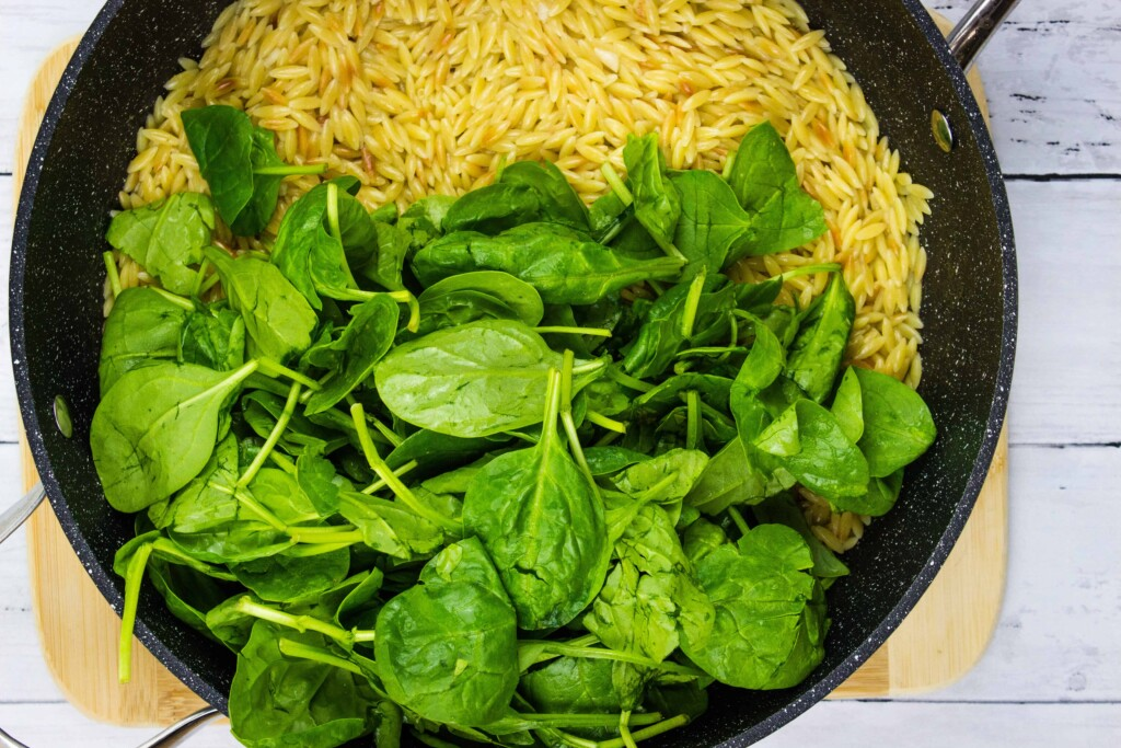 Folding the raw spinach into the hot orzo.