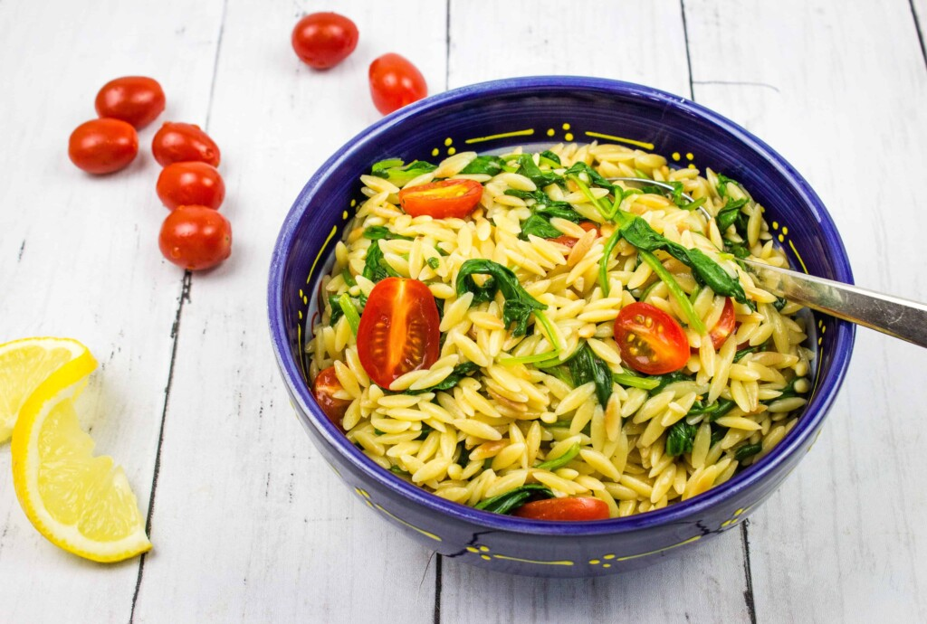 orzo with spinach and tomatoes in a serving bowl