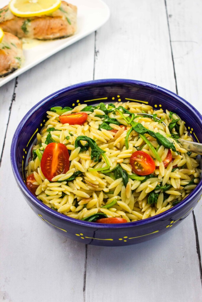 creamy orzo with spinach in a blue serving bowl