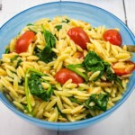 creamy spinach orzo with tomatoes in a blue serving bowl