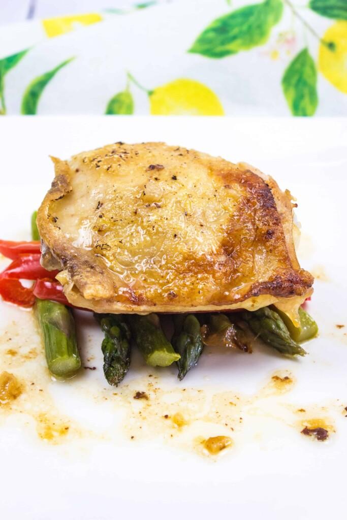 garlic chicken with asparagus on a white platter