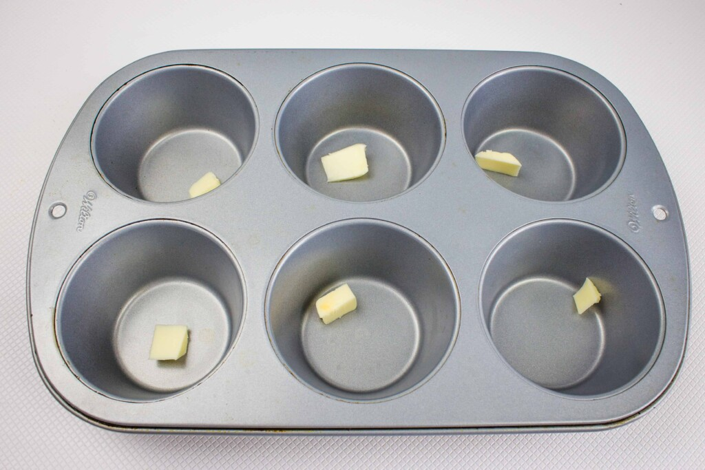 1/2 teaspoon of butter in each of the 6 muffin cups