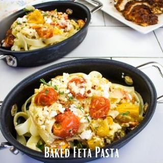 two servings of baked feta pasta in black oval bowls with roasted turkey in teh background