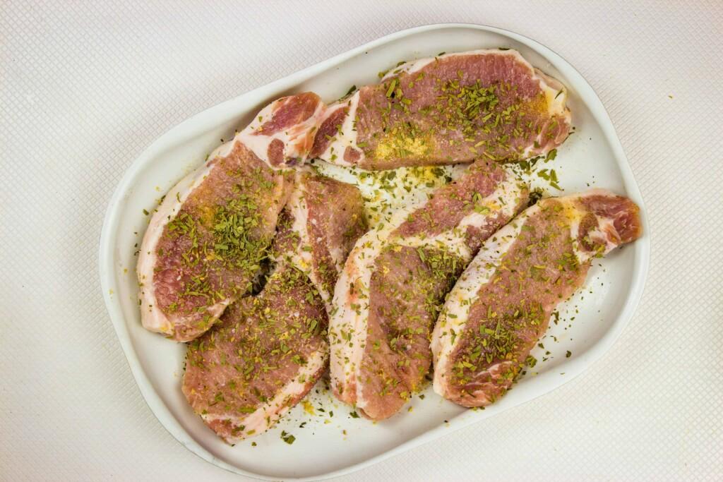 Boneless pork chops seasoned with salt, pepper, garlic powder and tarragon.
