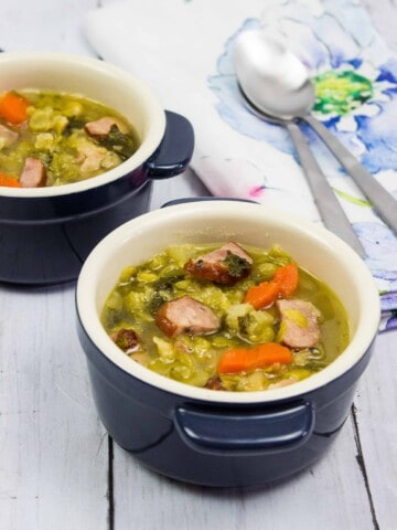 split pea, ham and sausage soup in two small bowls with spoons and a napkin in the background