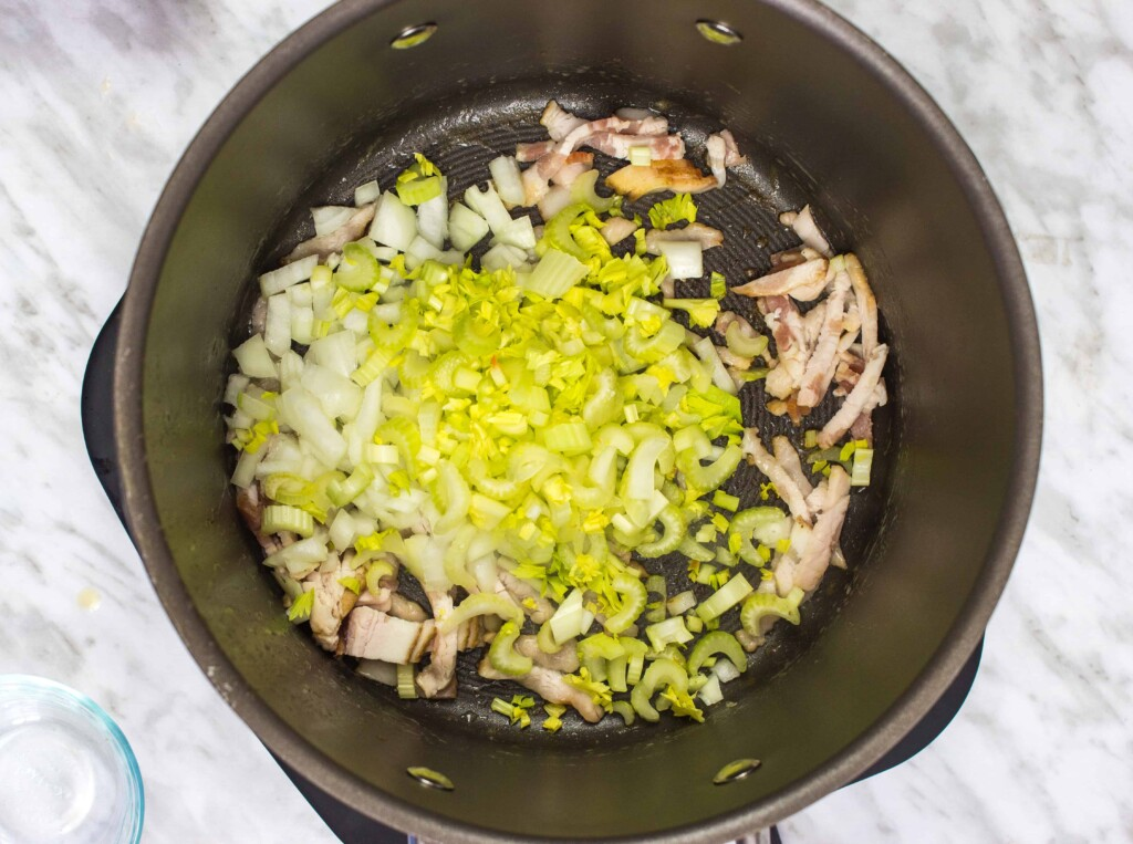 Adding the onions, celery, and bacon to the skillet.