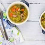 split pea, ham and sausage soup in two small bowls with spoons and a napkin