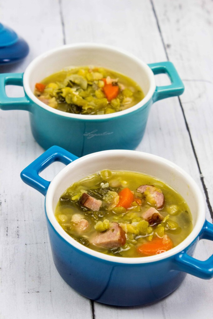 split pea soup with ham and sausage in two blue soup bowls