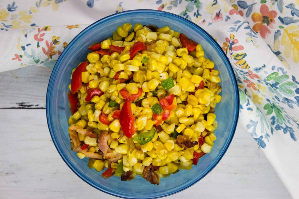 Texas corn succotash in a blue serving bowl with a floral napkin in the background