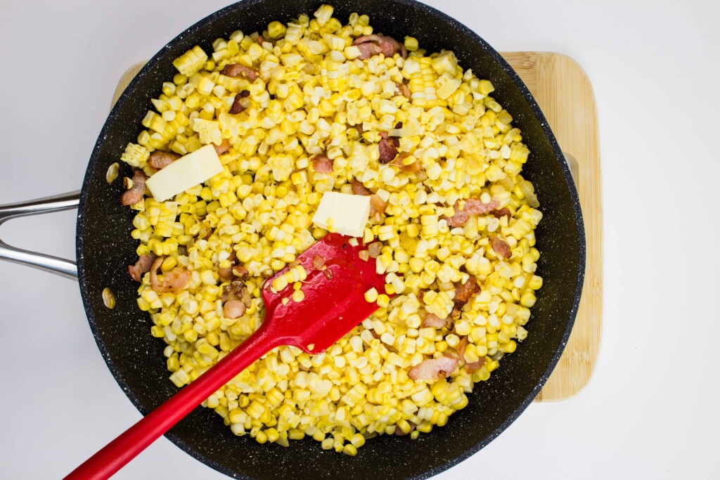 adding the butter and corn to the pan