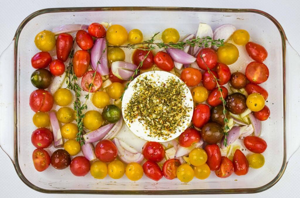 tomatoes, garlic, shallot and block of feta in a baking dish to make baked feta pasta
