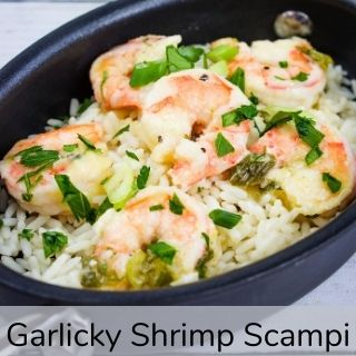 Garlicky shrimp scampi in a black oval dish.