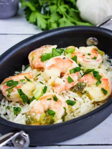 a closeup of shrimp scampi in a black oval serving dish