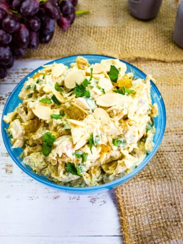 curry chicken salad with grapes in a bloue serving dish