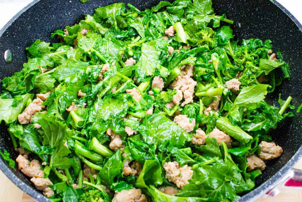 adding the chopped broccoli rabe to the skillet