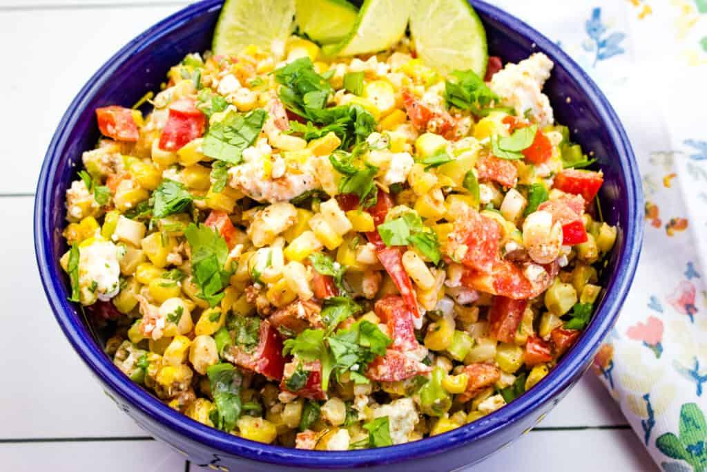 a closeup of mexican street corn salad in a blue bowl