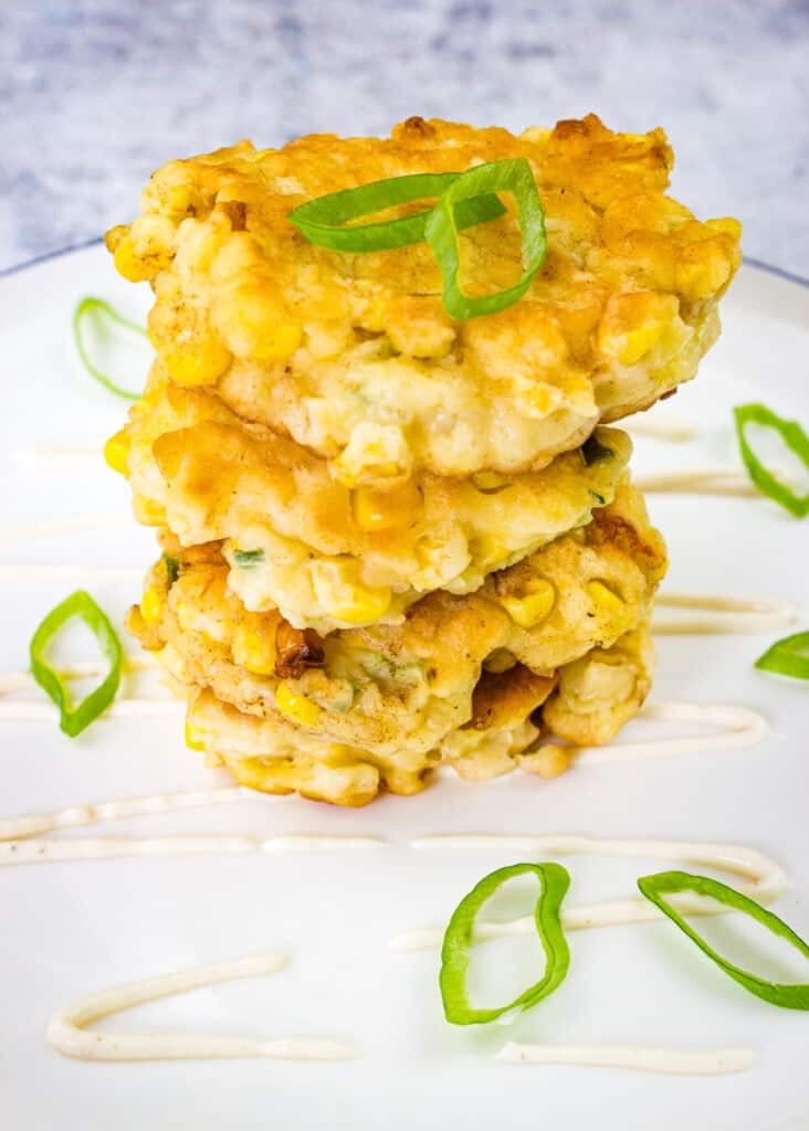 corn fritters with jalapeno and applewood smoked cheddar in a stack