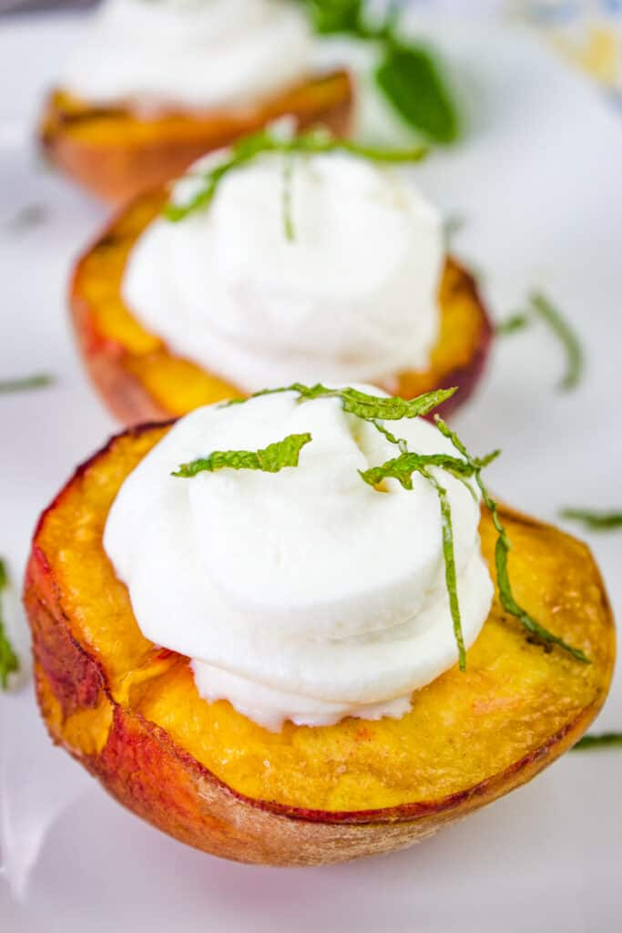 smoked peaches with spiced rum whipped cream on a platter