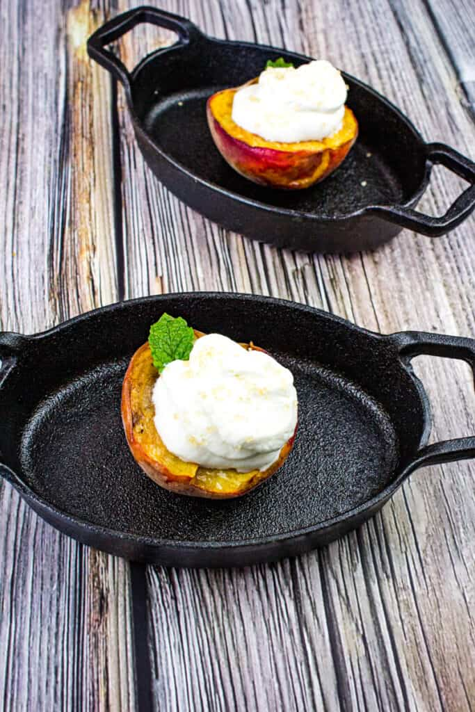 smoked peaches with spiced rum whipped cream in black dishes
