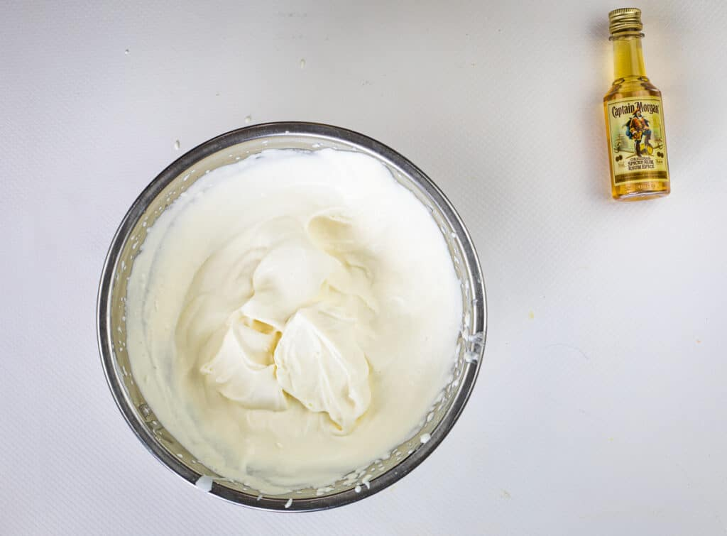 spiced rum whipped cream with stiff peaks in a bowl