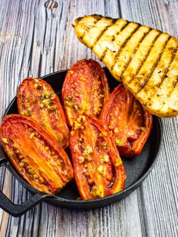 smoked tomatoes in a black bowl with grilled bread on the side