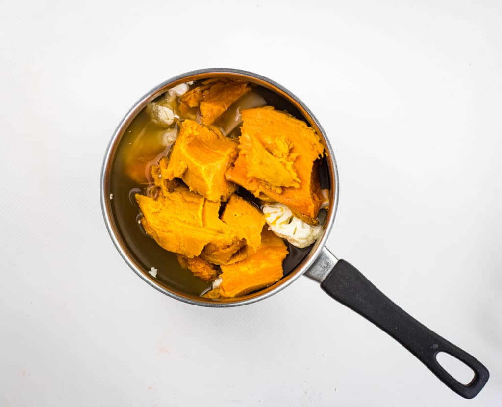 simmering the cauliflower and sweet potato in a pot with broth