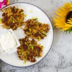 crispy corned beef fritters on a white plate with sour cream