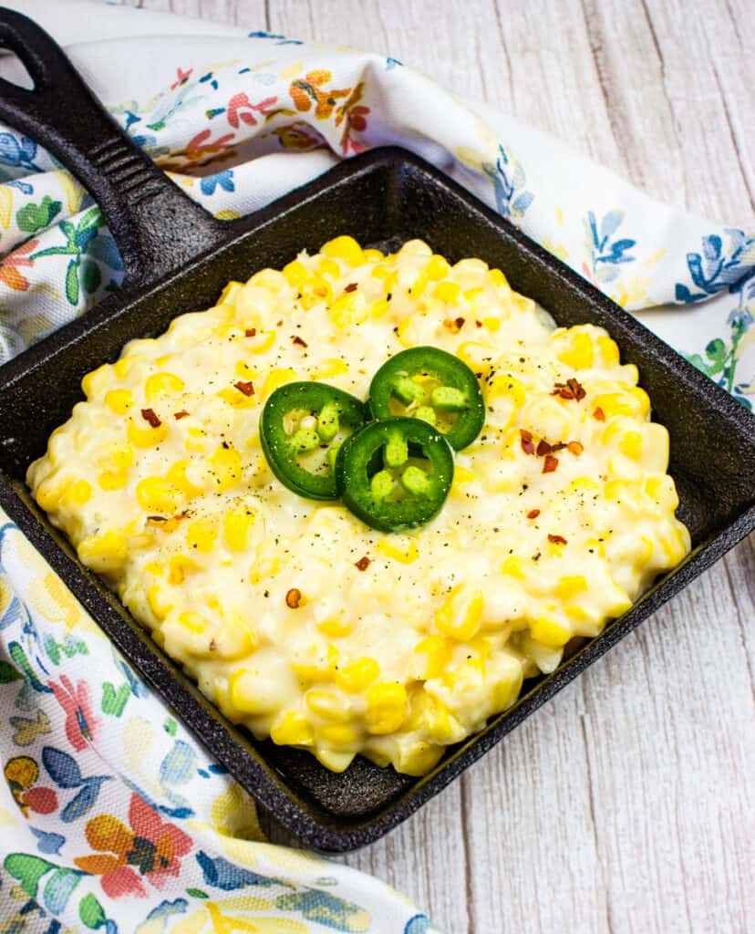 creamed corn in a black serving dish