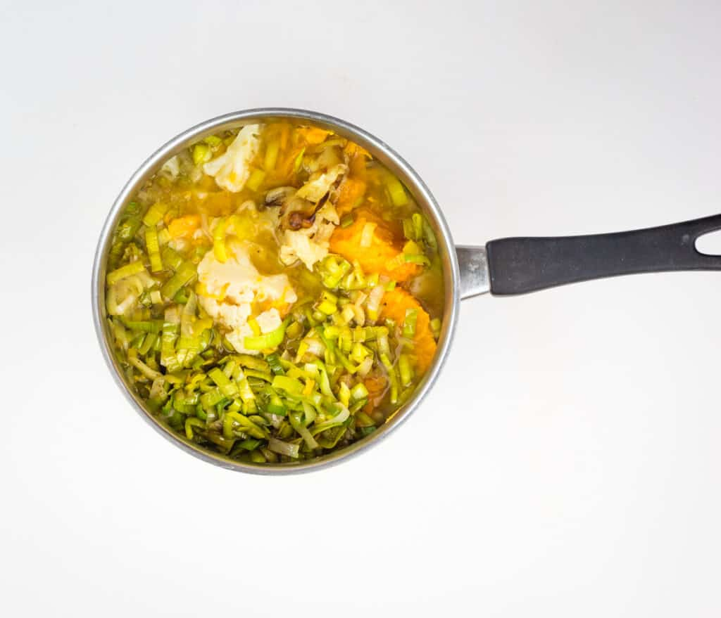 simmering the cauliflower and sweet potato soup ingredients in a pot