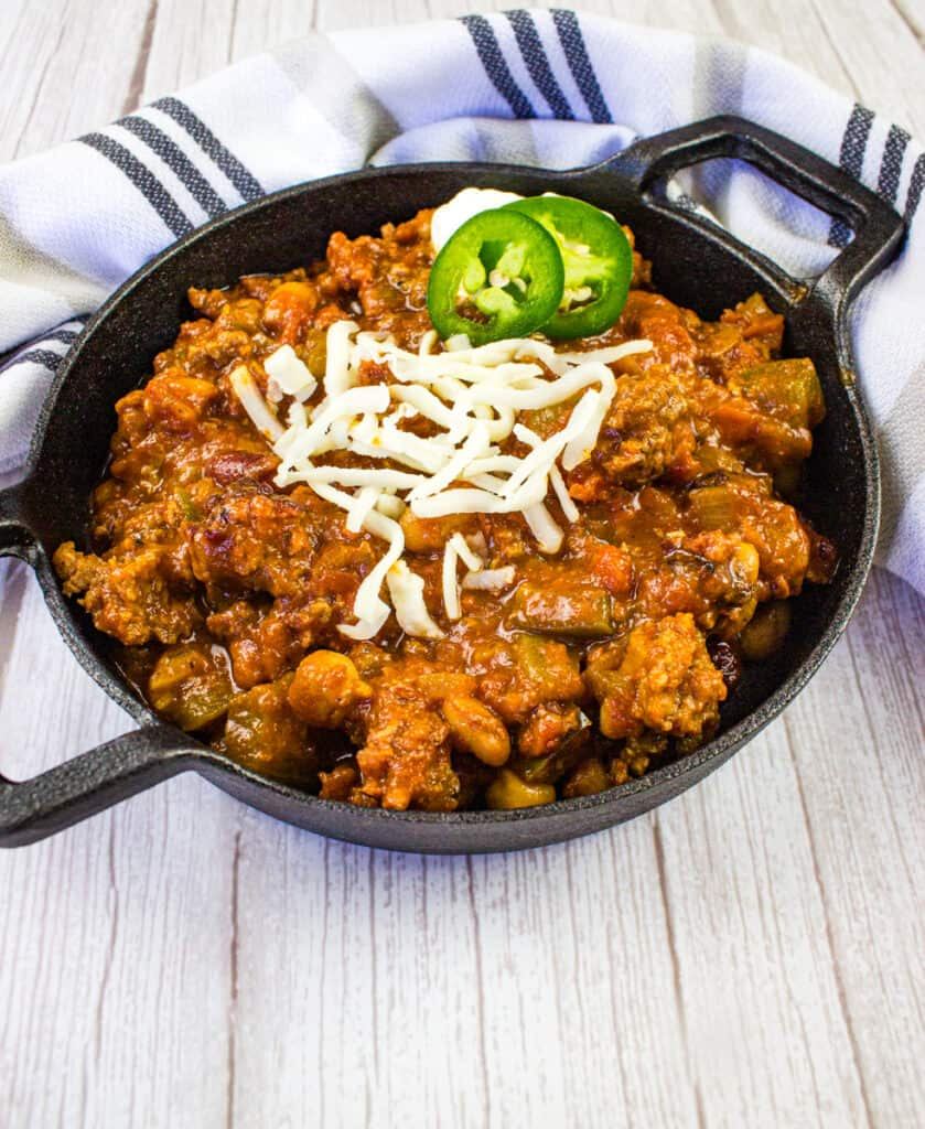 over the top chili in a black serving dish