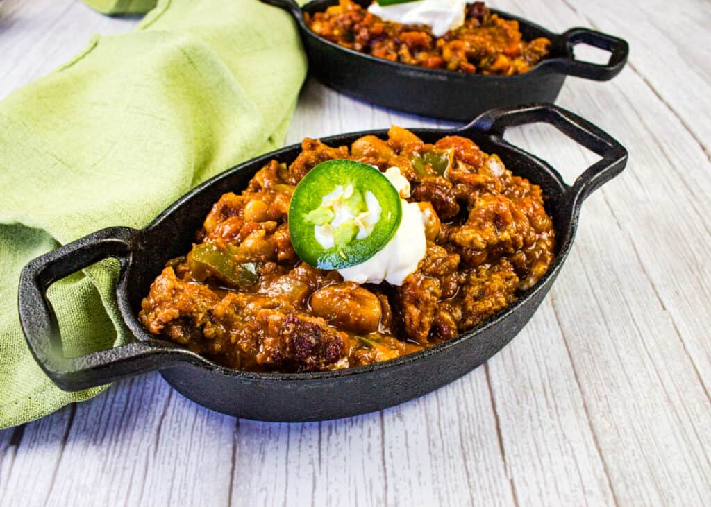 Over the top chili in black cast iron pans
