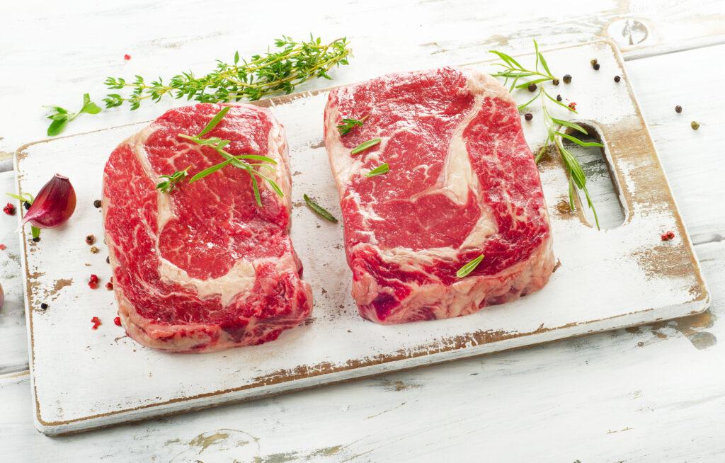 ribeye steaks on cutting board