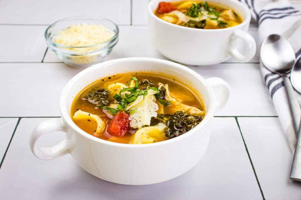 tortellini soup with kale and chicken in white soup bowls