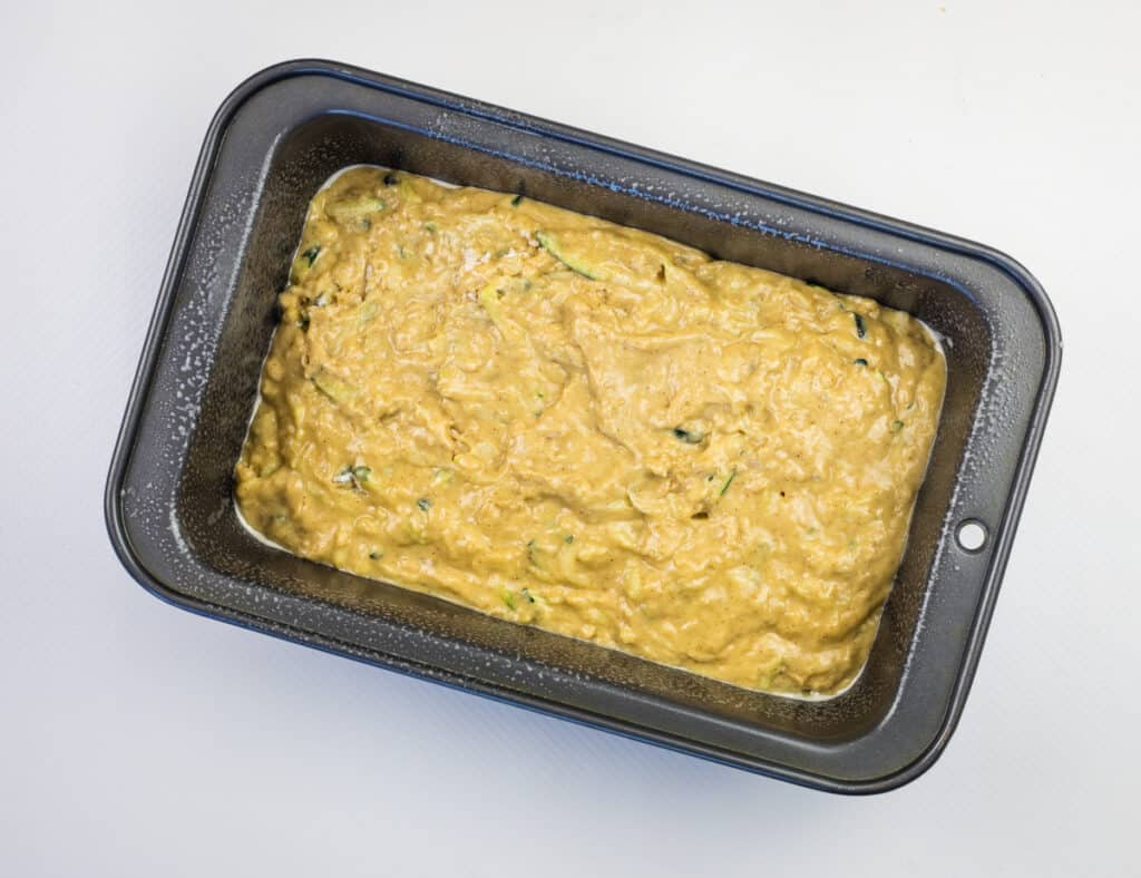 add zucchini bread batter to a loaf pan and bake
